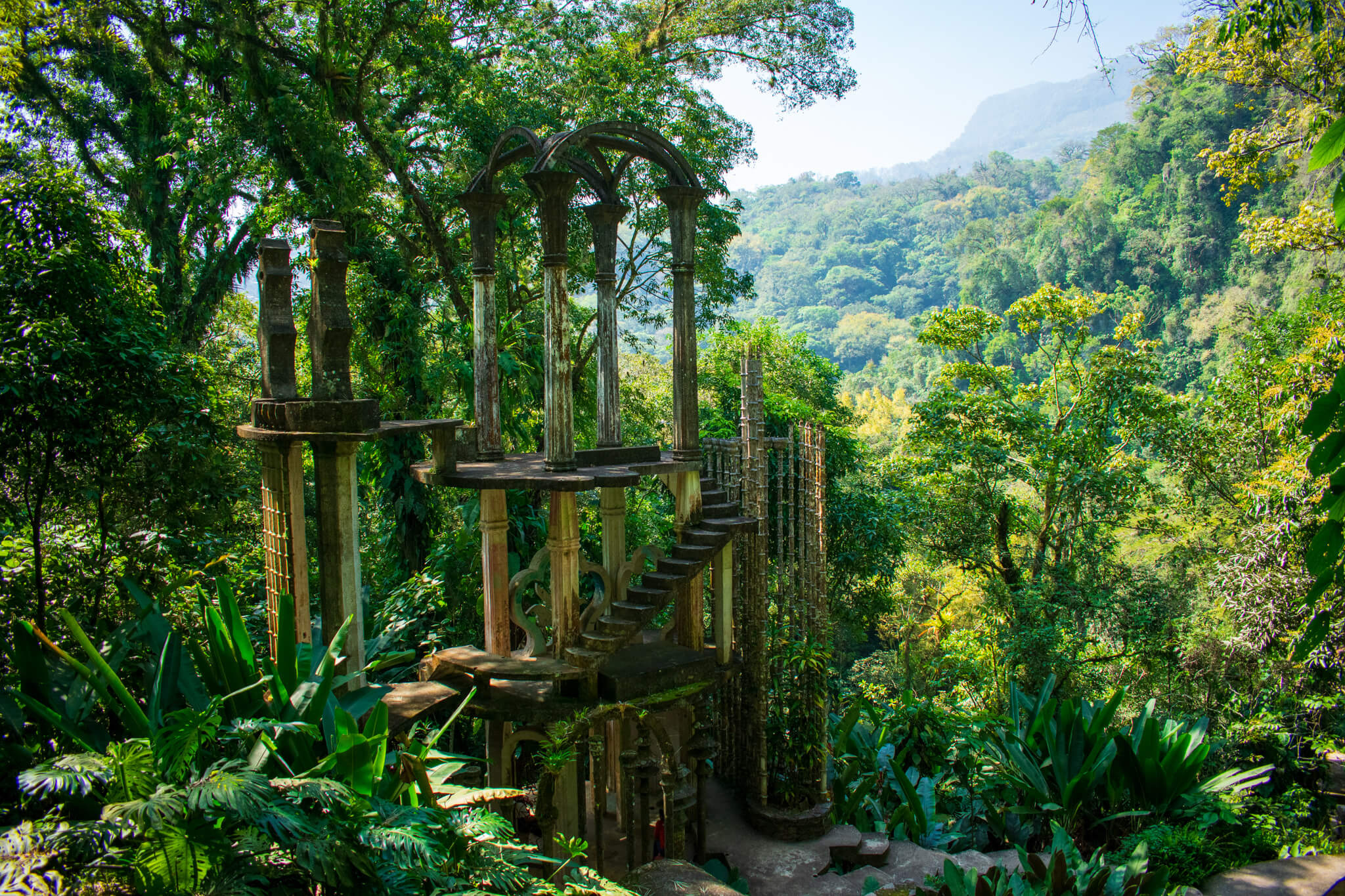 Surrealist garden sculpture in Los Pozas de Xilitla, Mexico with mountain vista in background.