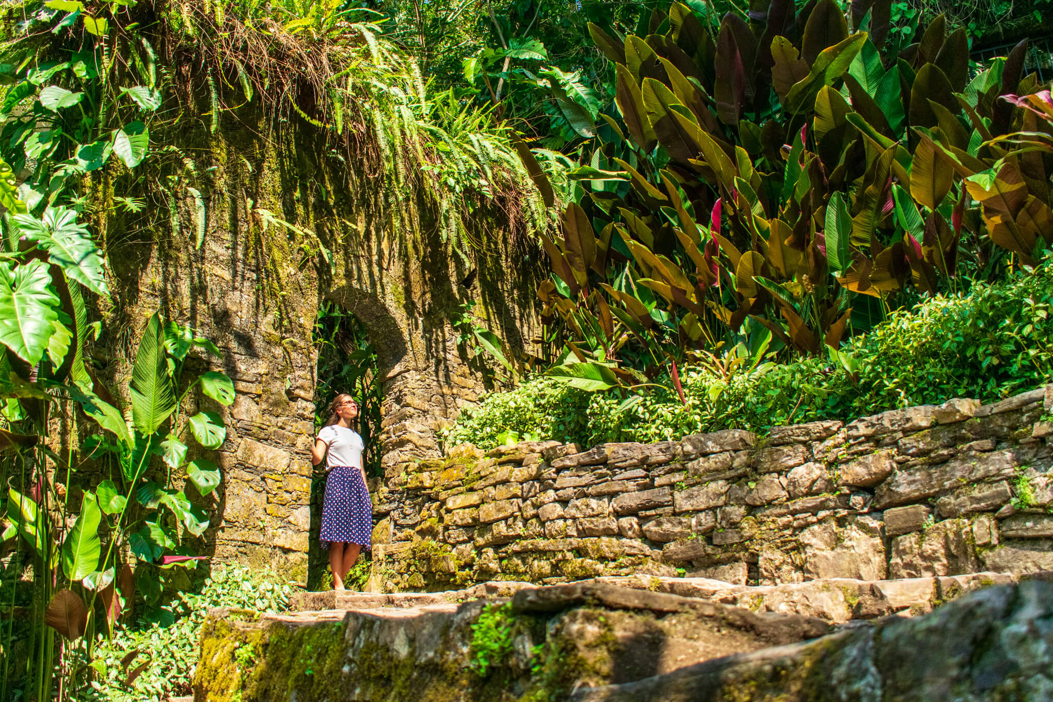 Girl under stone arch in jungle garden of Los Pozas de Xilitla, Mexico.