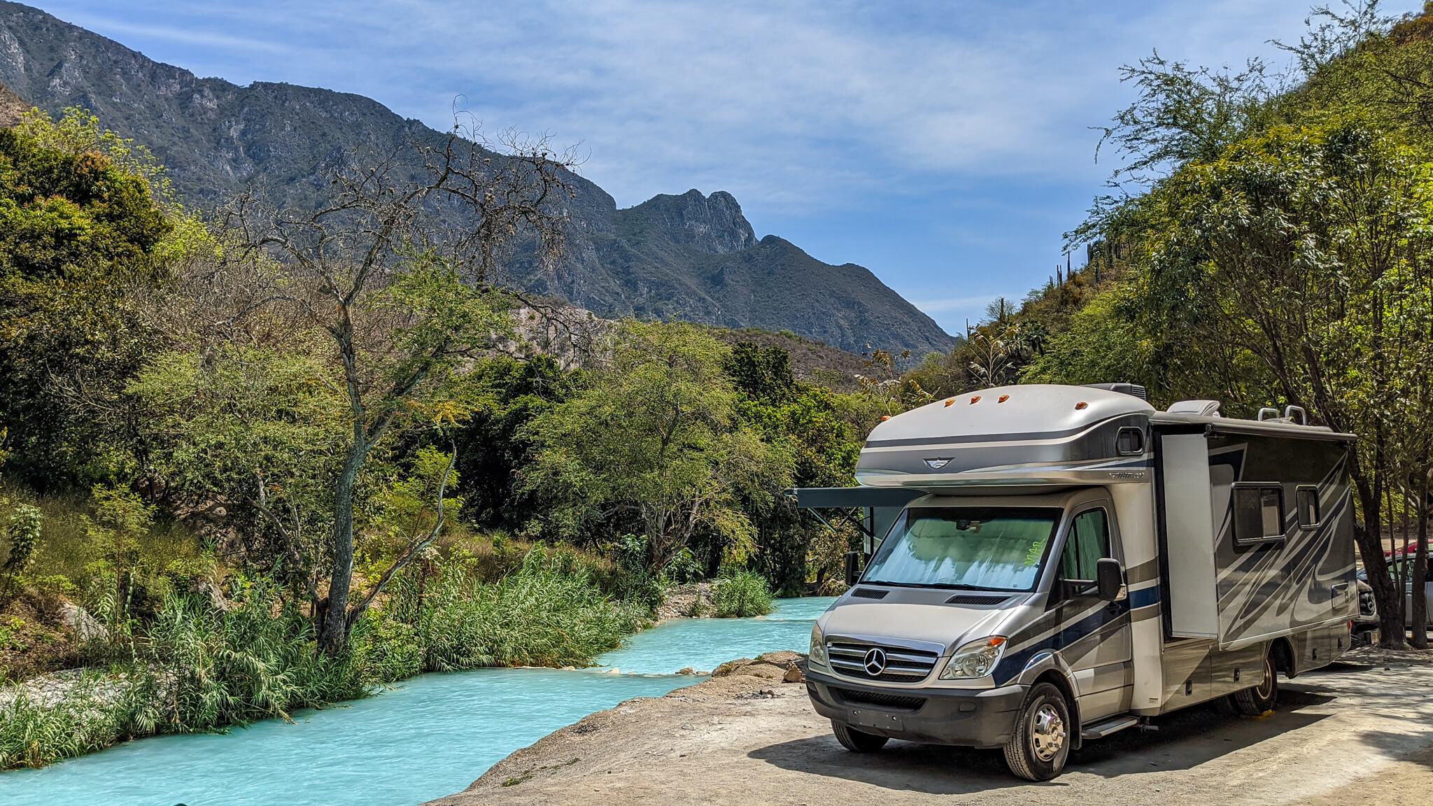 Class C RV next to turquoise thermal river RV Mexico