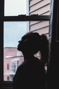Silhouette of sad woman looking out window
