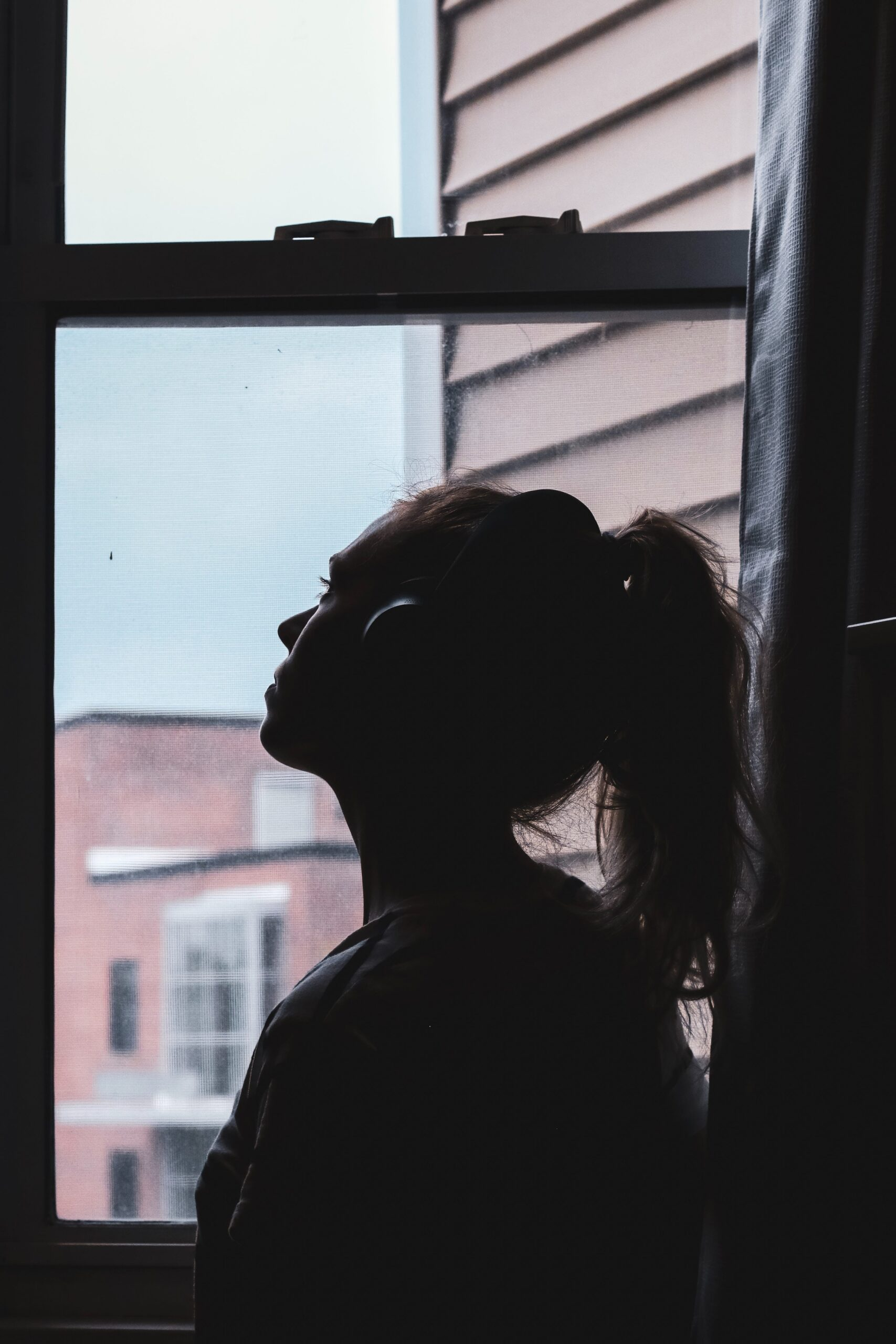 Silhouette of a woman standing in a window