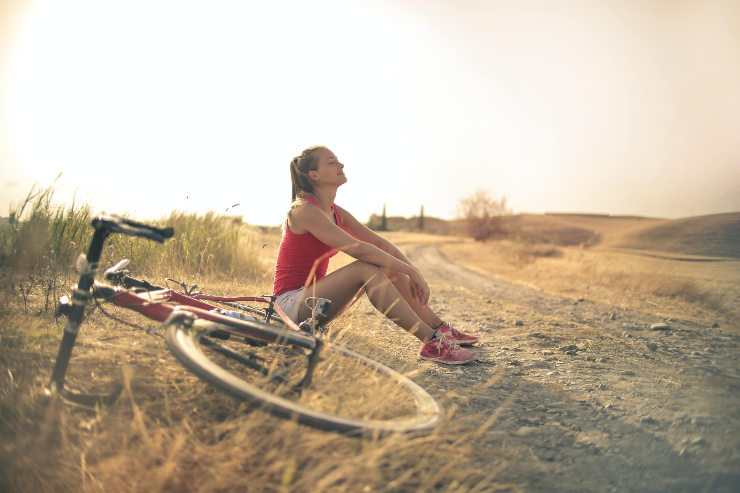 Woman with face to the sun and bicycle