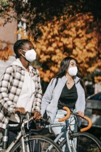Two women wearing masks with bicycles