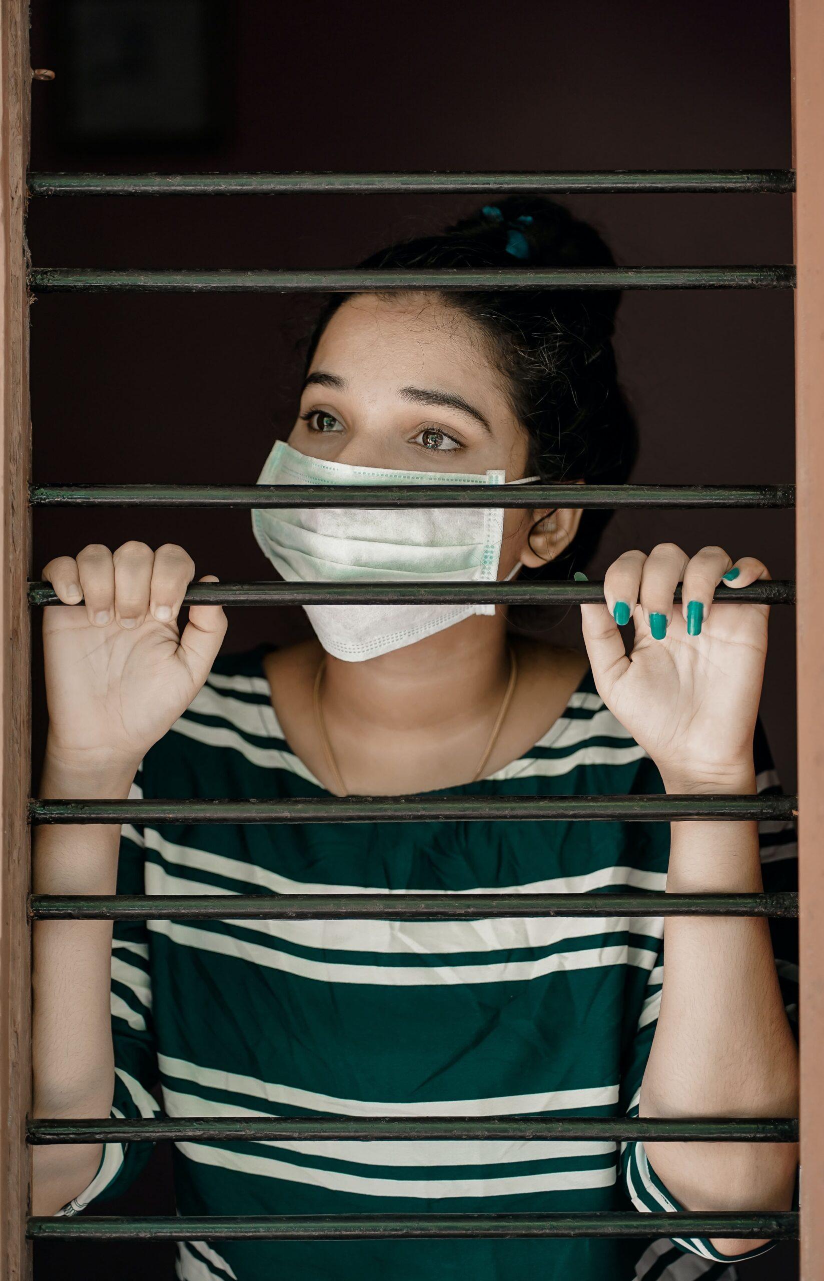 Woman looking outside between window bars