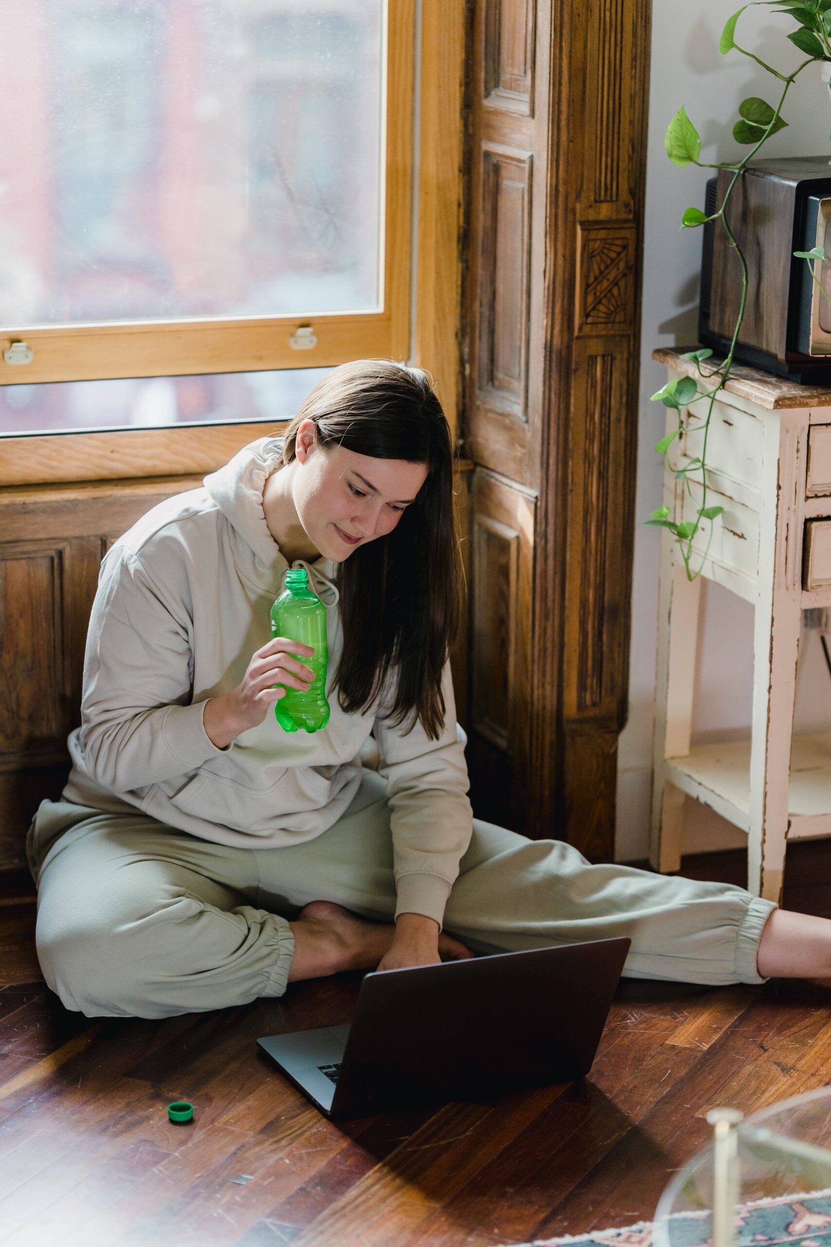 Content woman sitting on floor with laptop