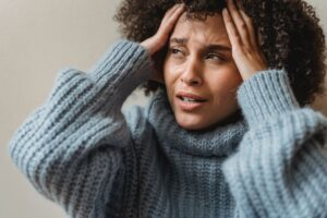 Distraught woman in blue turtleneck