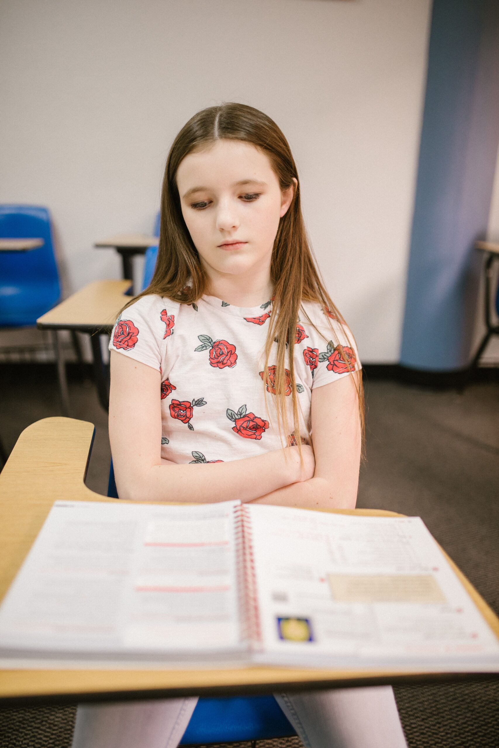 Girl sitting in desk arms folded looking down