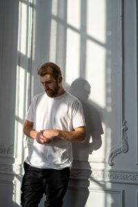 Man leaning against wall looking down wringing hands