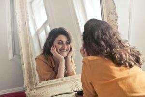 Woman looking in mirror smiling