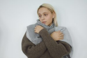 Anxious woman wearing sweater and wrap