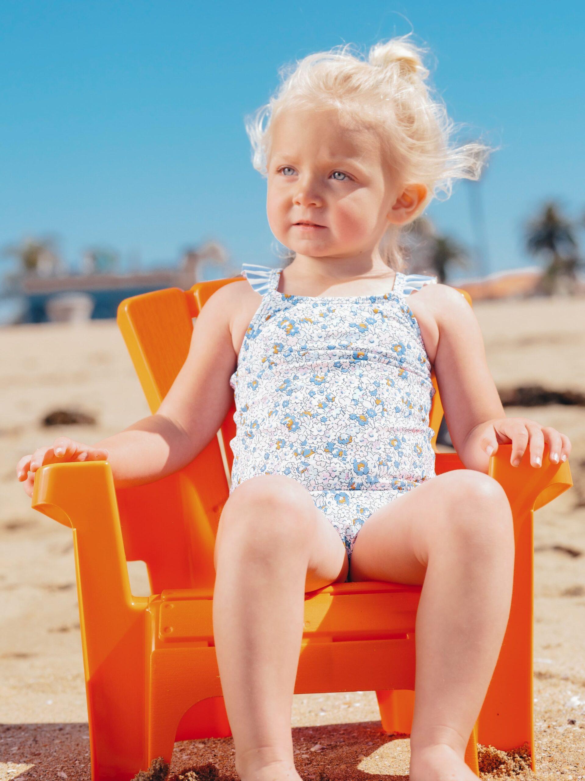 Blonde girl sitting in chair on beach