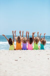 Group of women on beach with arms raised