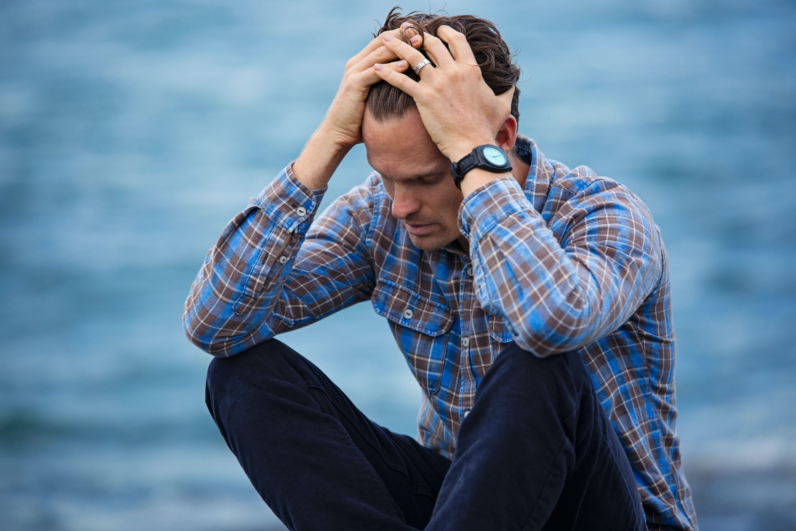 Man sitting next to water holding his head