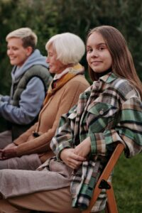 Girl leaning on chair next to family