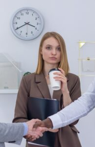 Woman in office with coffee cup and two people shaking hands