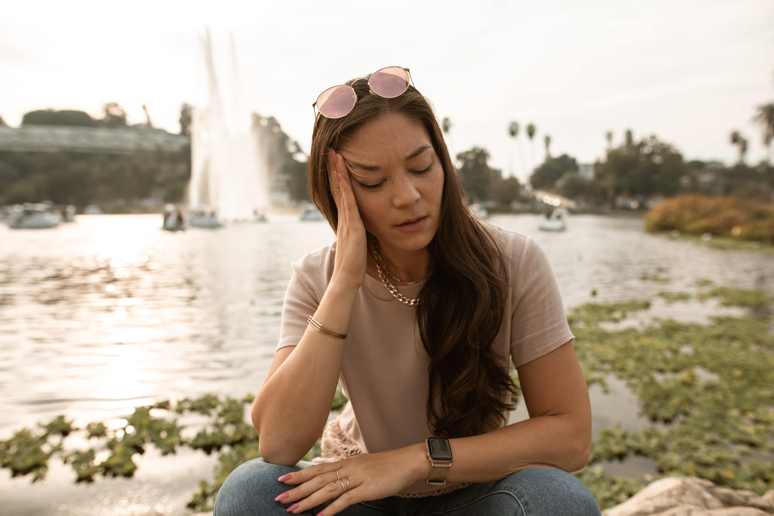Woman sitting next to water holding her head