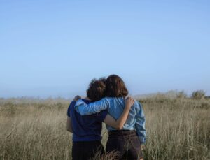 Couple with arms around each other in a field