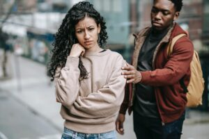 Woman appearing troubled with man reaching for her