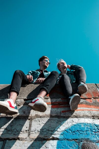 Man and woman sitting on top of a concrete wall