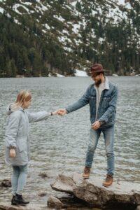 Couple climbing on rocks in water