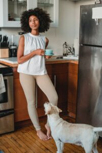 Woman in kitchen with tea cup and dog