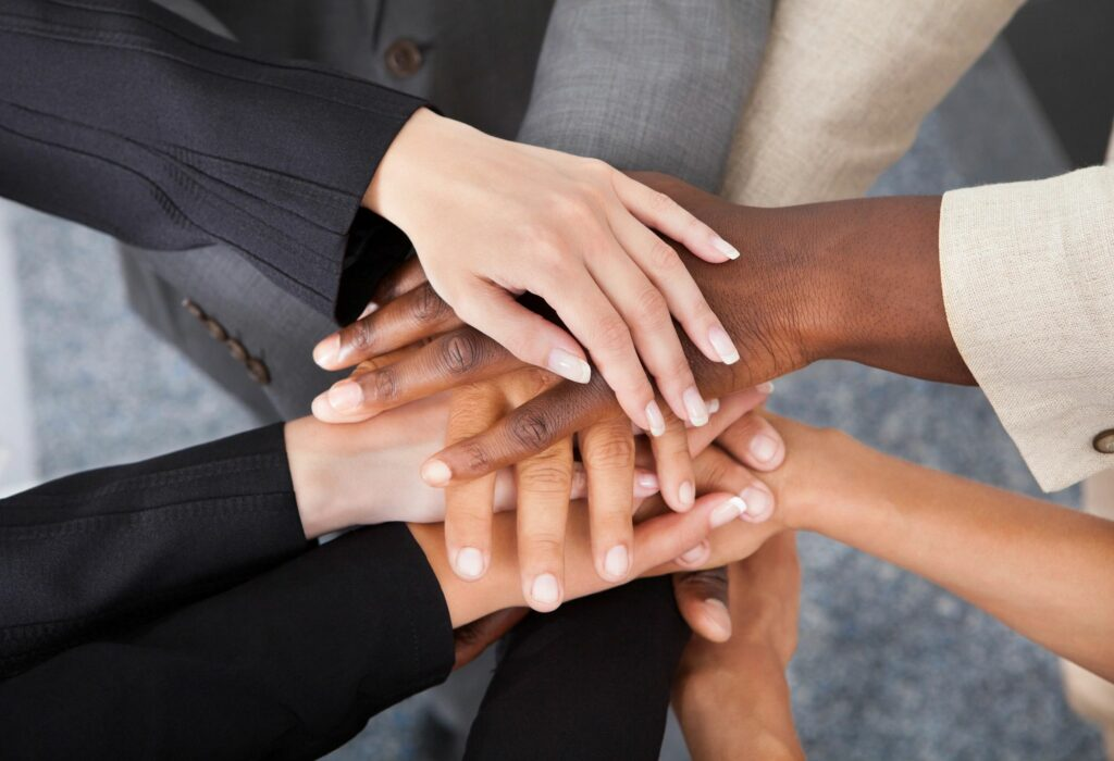 Multiple ethnic peoples hands stacked in agreement