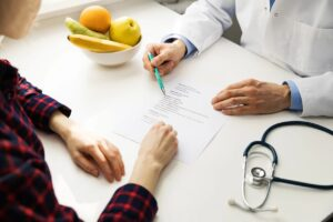 Doctor holding pen going over notes on paper with patient