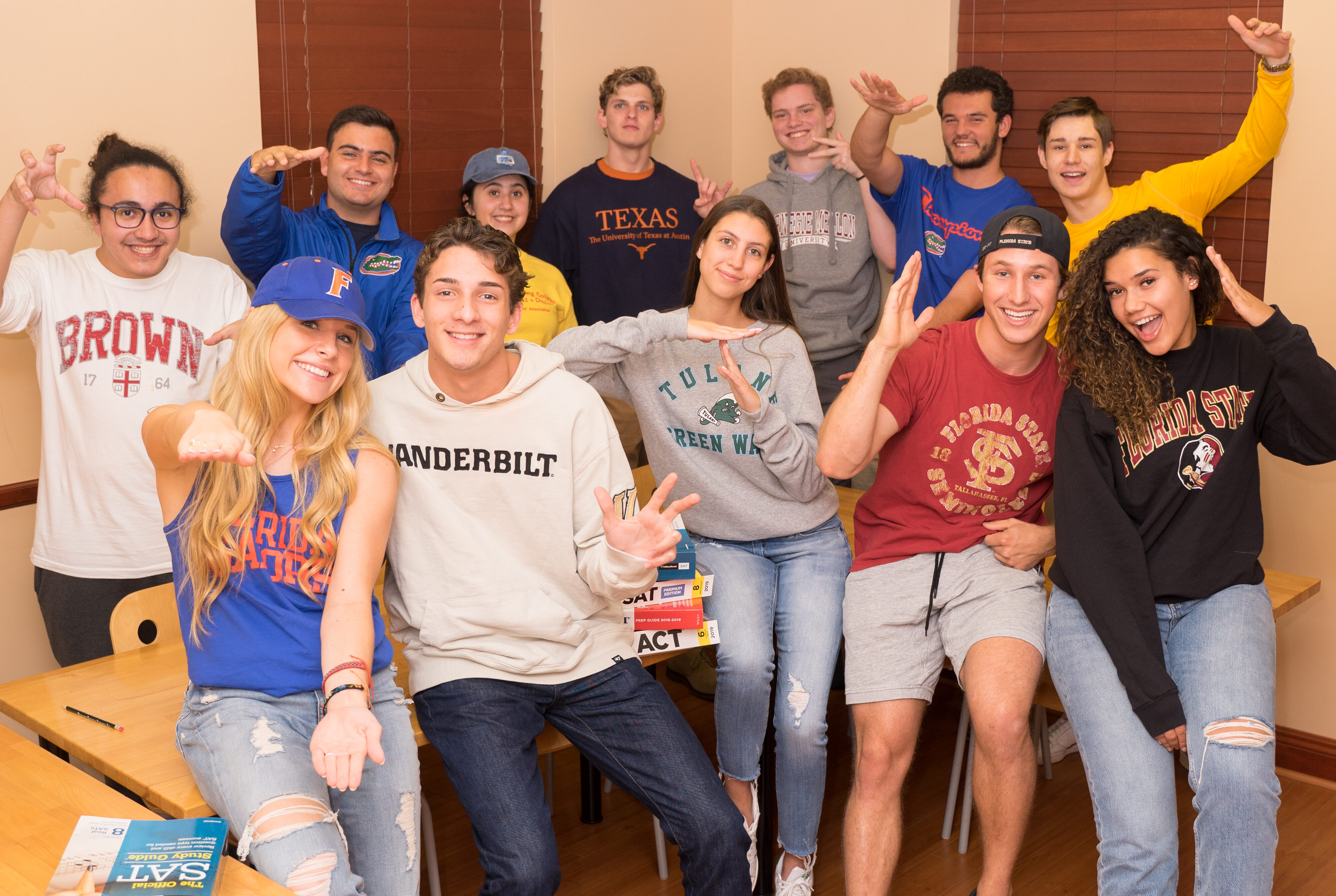 Group of high school seniors wearing the gear from the colleges that they were admitted to