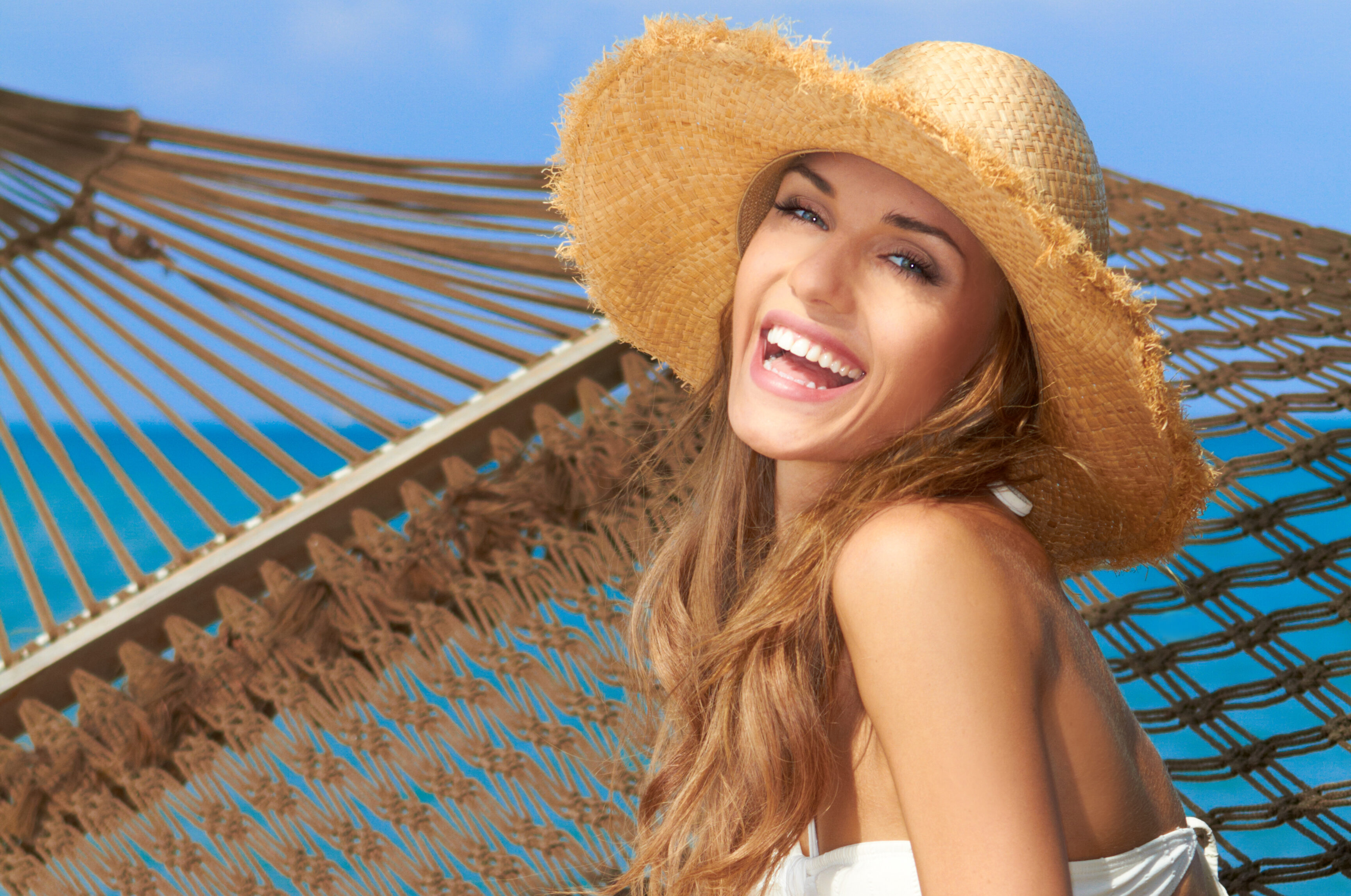 Vivacious happy woman sitting elegantly on a hammock in a bikini and wide brimmed straw sun hat