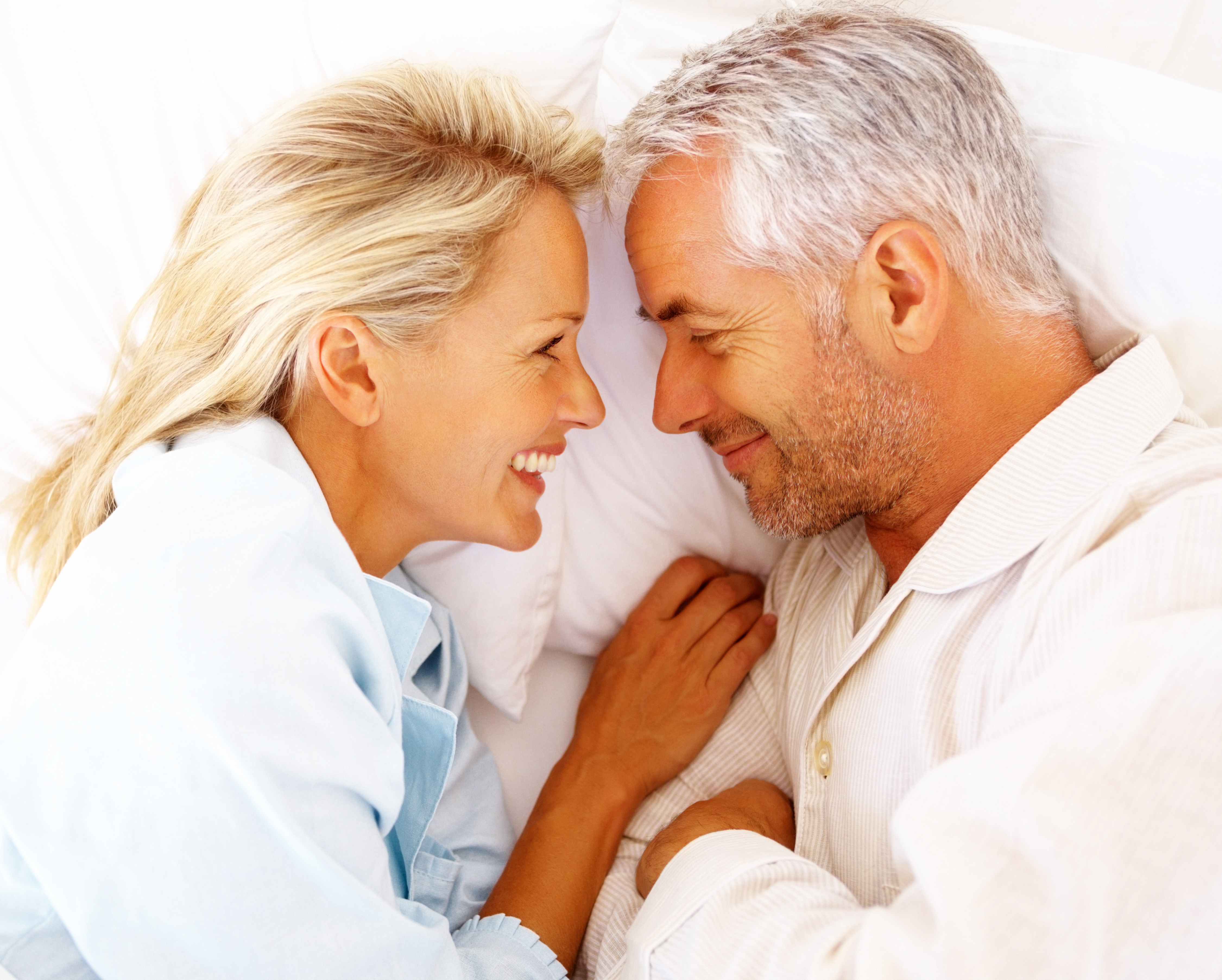 Attractive mature couple laying facing each other