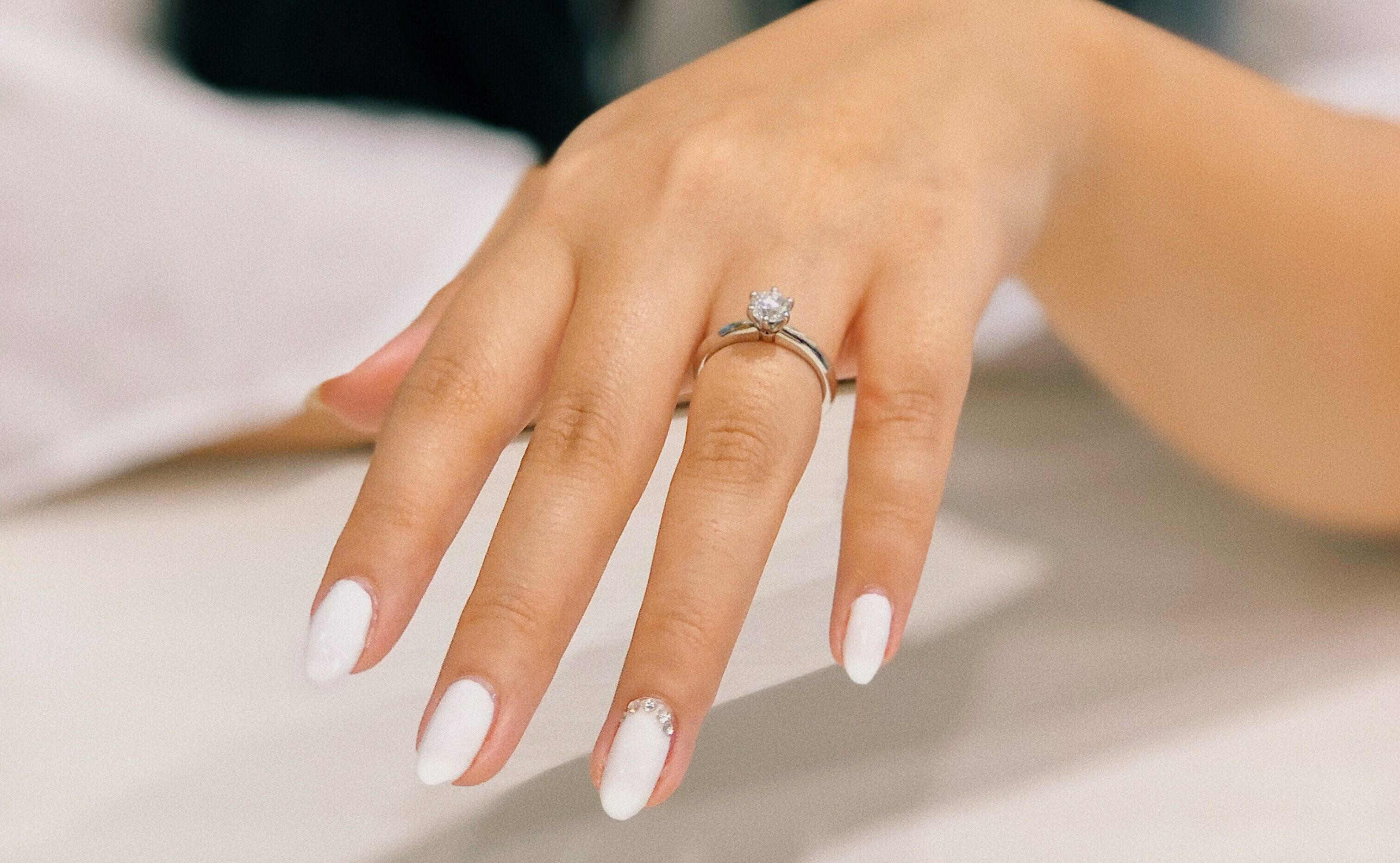 Smooth hand with fresh manicure and engagement ring