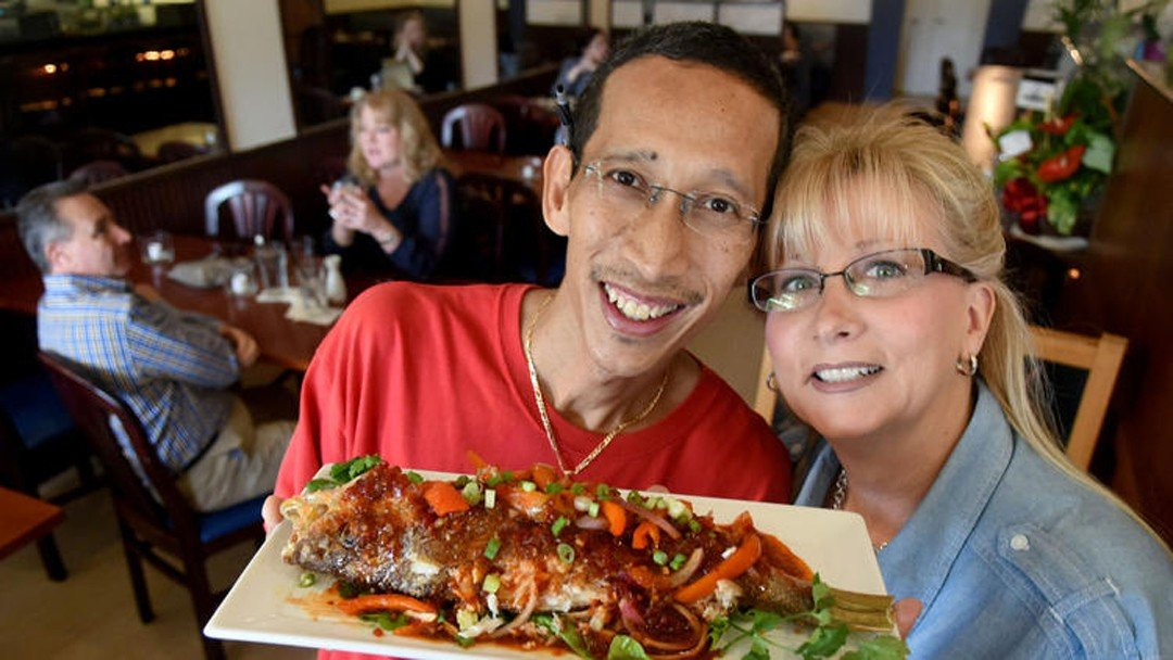 Eddie and a woman showing off a dish