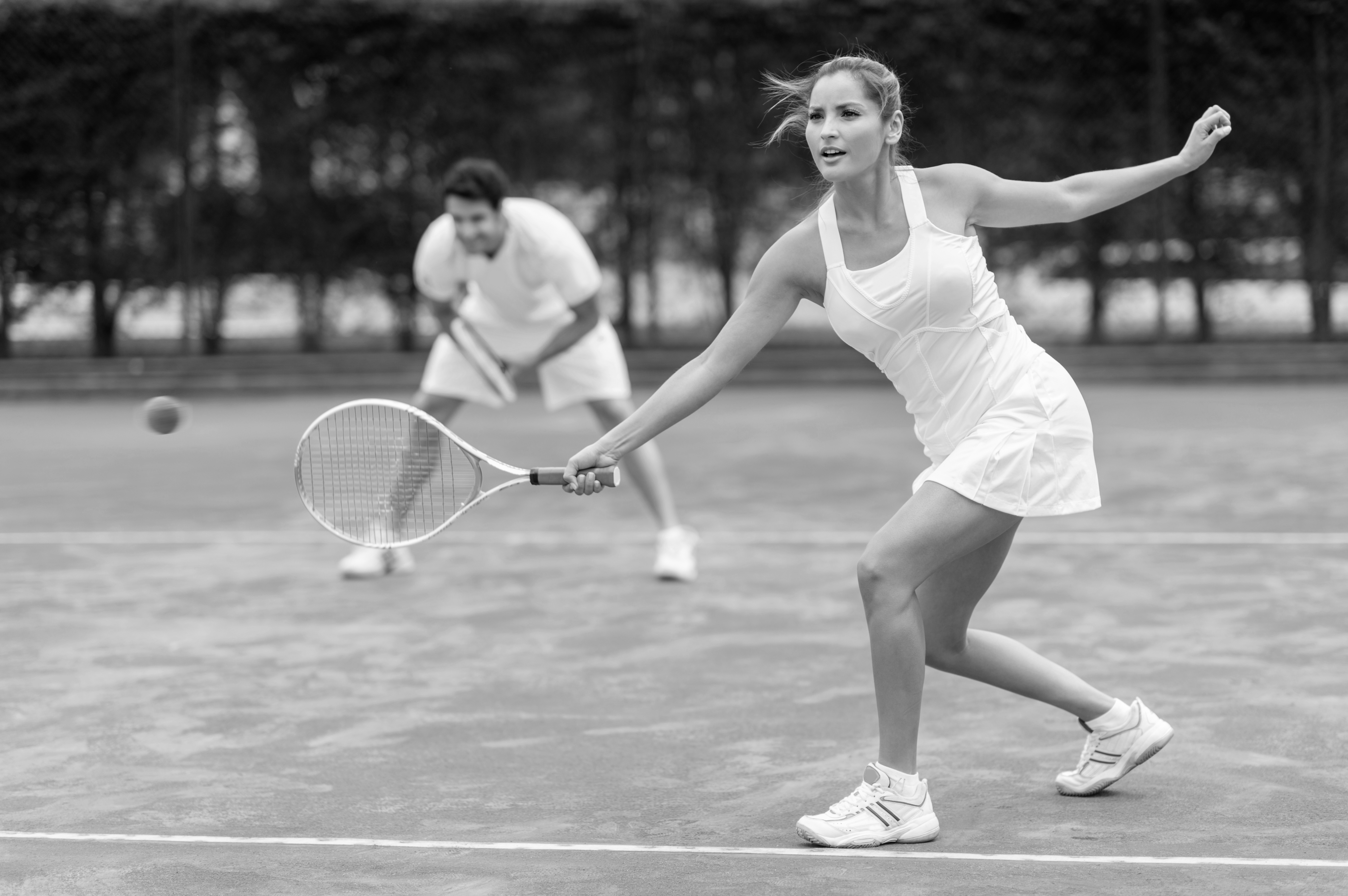 woman hitting a tennis ball with teammate standing behind her