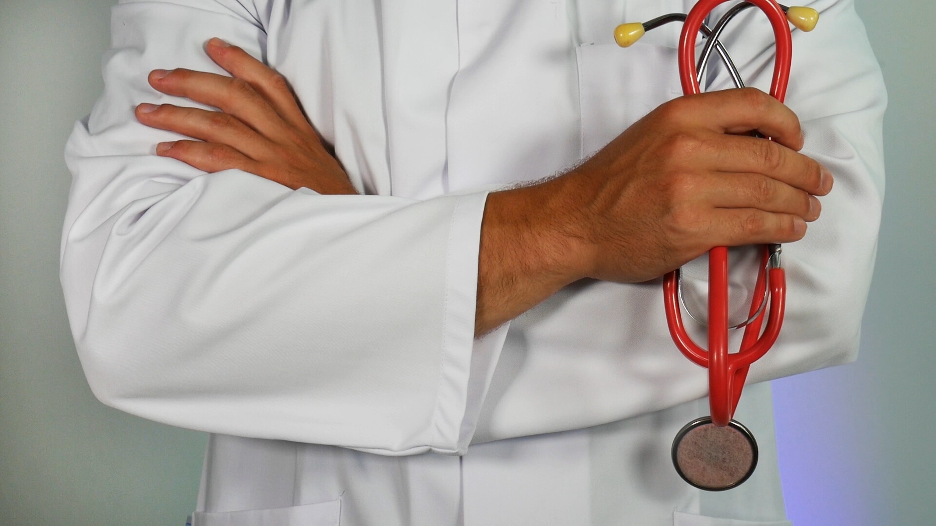 crossed arms of a doctor holding medical equipment in his right hand