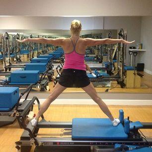 woman on exercise machine doing split