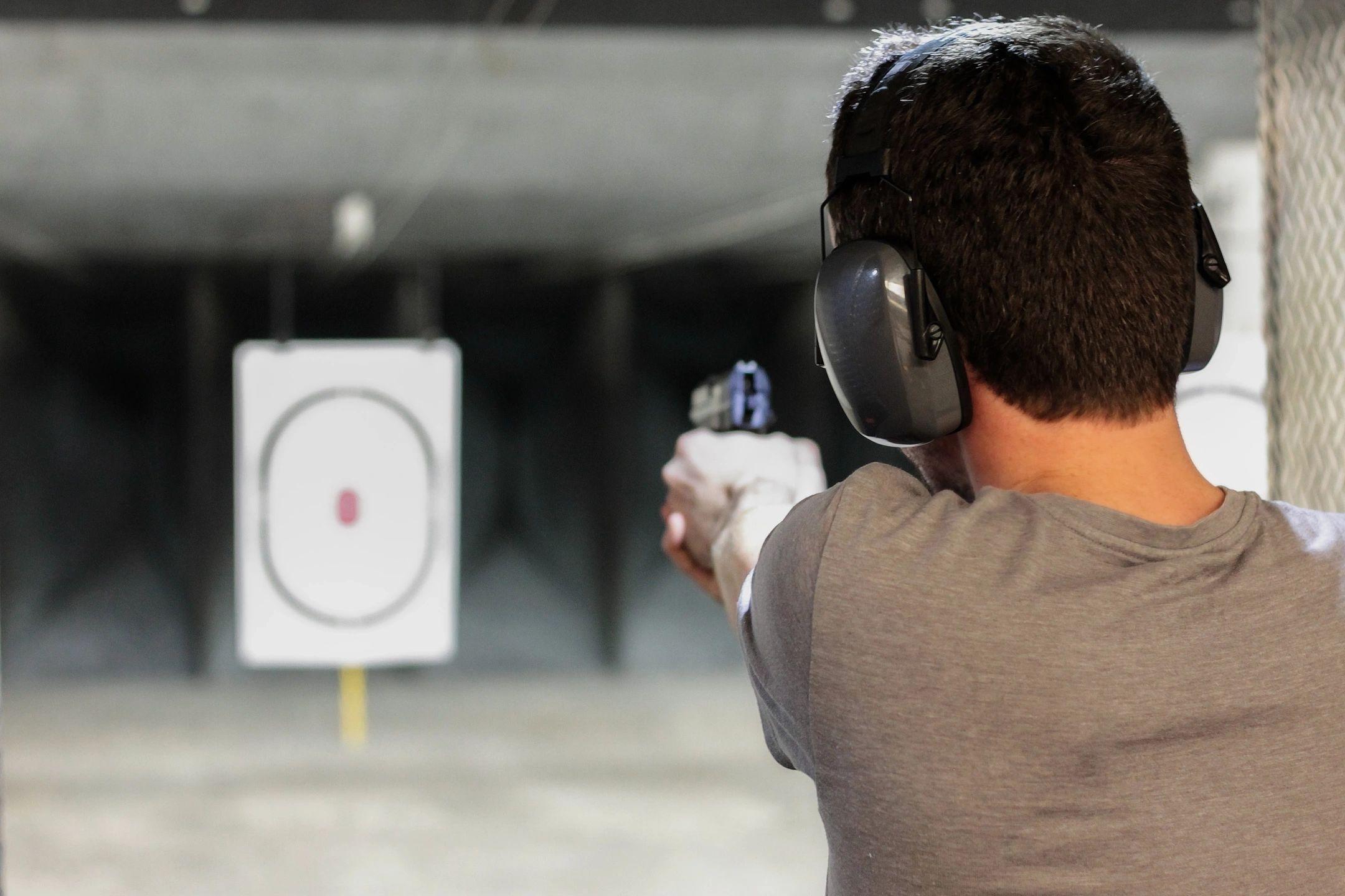 Back of man aiming pistol downrange at target