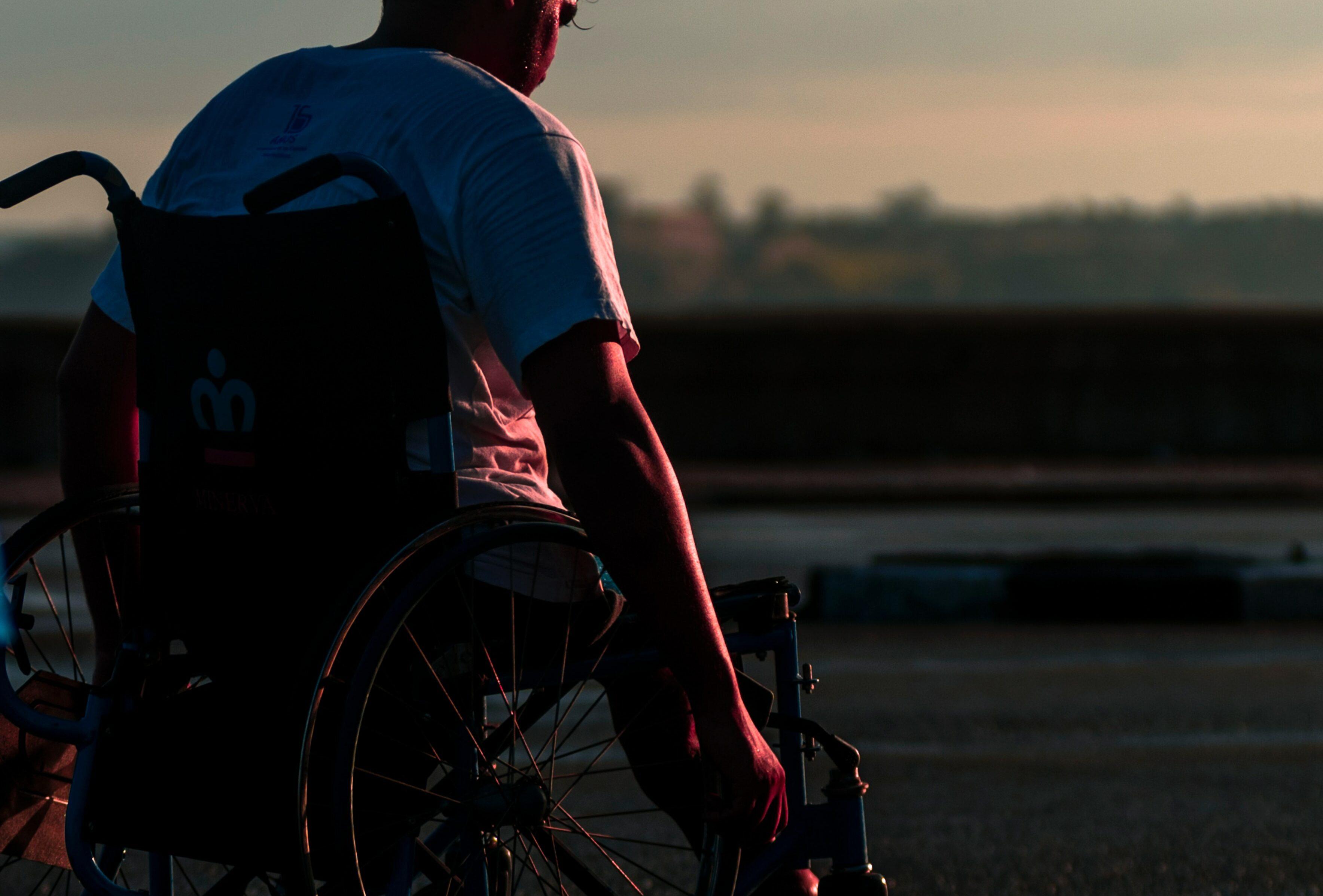 man in wheelchair facing sunset