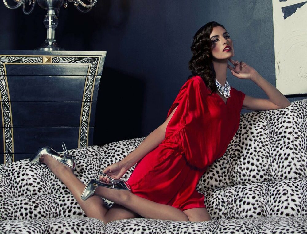 Beautiful woman on couch wearing red dress