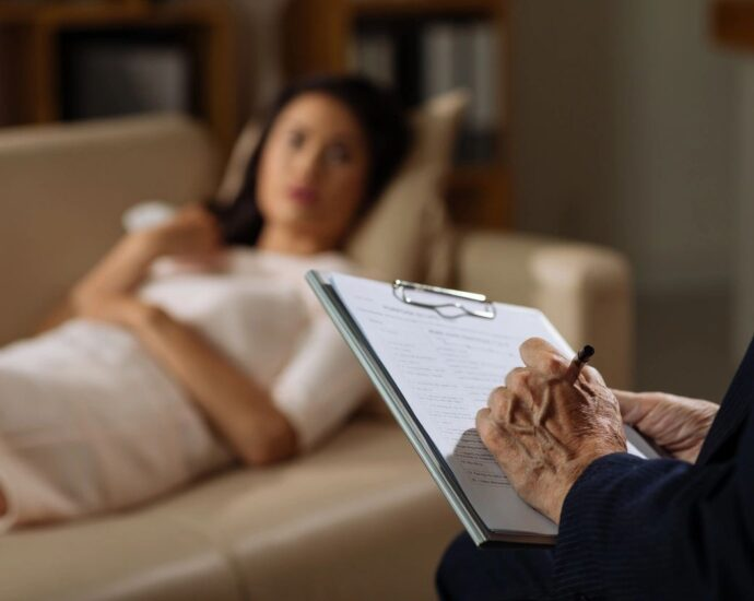 woman on couch with person taking notes