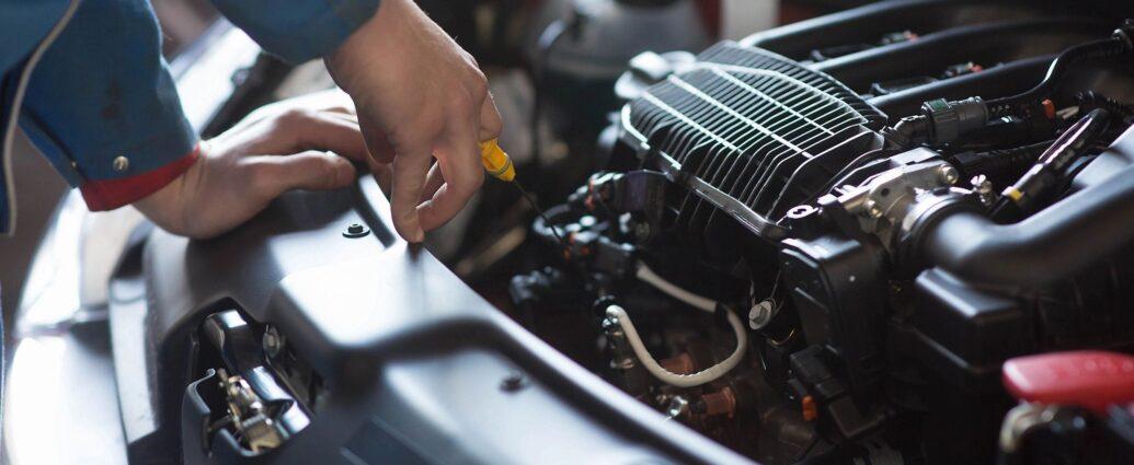 mechanic checking oil level in car