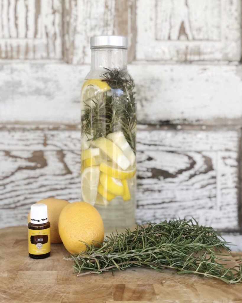 beautiful bottle of dishwasher rinse aid. Lemon slices and rosemary sprigs inside a glass jar with white vinegar.