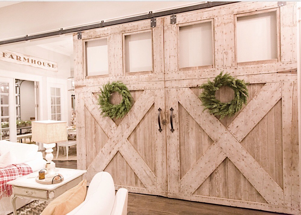 large carriage house barn doors in my living room that are decorated with live greenery wreaths