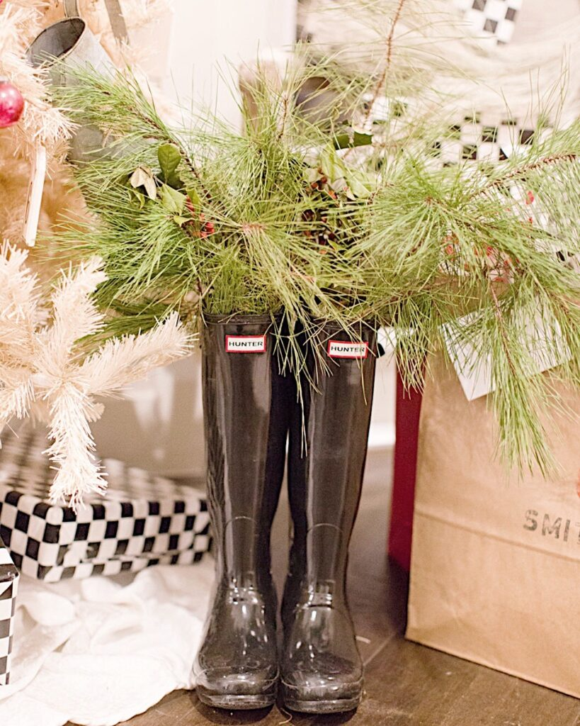 Black Hunter rain boots filled with greenery stand beside the kitchen Christmas tree