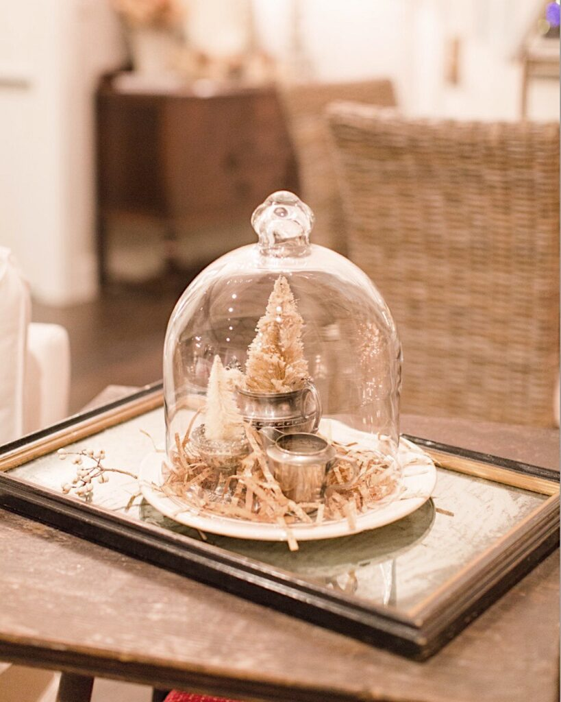 a vintage mirror is used as a tray for table decor.  A small plate with several small cream color Christmas tree are on the plate and underneath a glass cloche