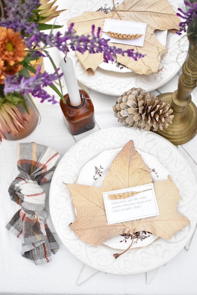 fall place setting with white dinner plate, brown transferware plate, and a large dried wreath on top of the plate.  A plaid napkin tied in a knot is to the left of the plate.