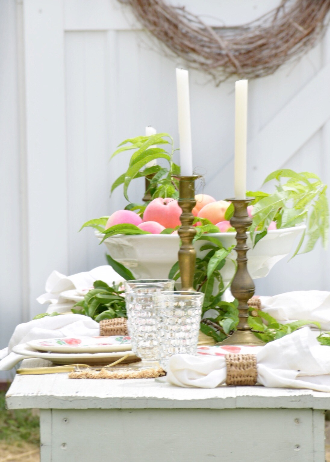 peach themed tablescape set at a long white farmtable. White dinner plates are topped with a peach pattern melamine plate and a white linen napkin with a woven napkin ring sits beside each place setting. The center piece is a large pedestal white bowl filled with fresh peaches and peach tree leaves, and 3 vintage brass candlesticks with white tapers surround the centerpiece.