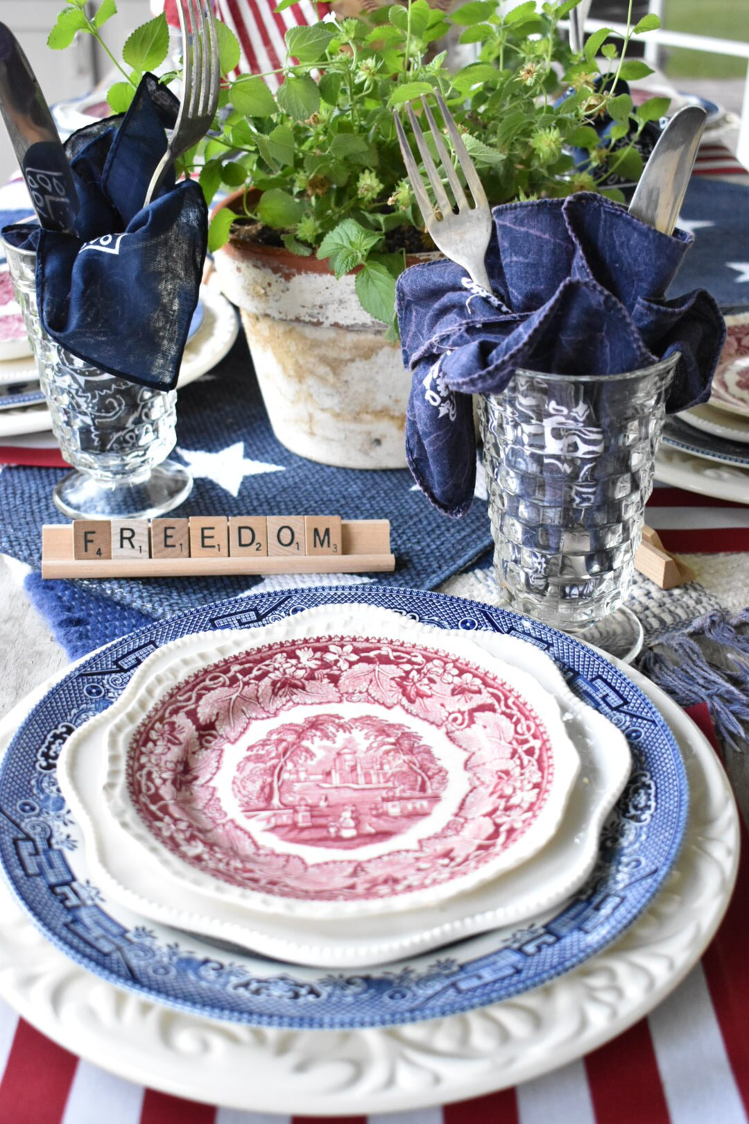 """a red, white and blue table setting with a stack of plates at each place setting placed on top of a 12x18"""" flag used as a placemat. A white dinner plate, then a smaller blue transferware dinner plate, a fluted edge white salad plate topped with a red transferware salad plate. A blue bandana for a napkin and silverware are standing inside a clear glass goblet. Scrabble tiles with a patriotic word are at each place setting."""