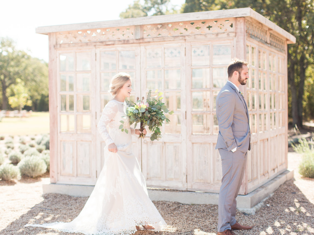 bride and groom first look photo beside a greenhouse in a lavender garden