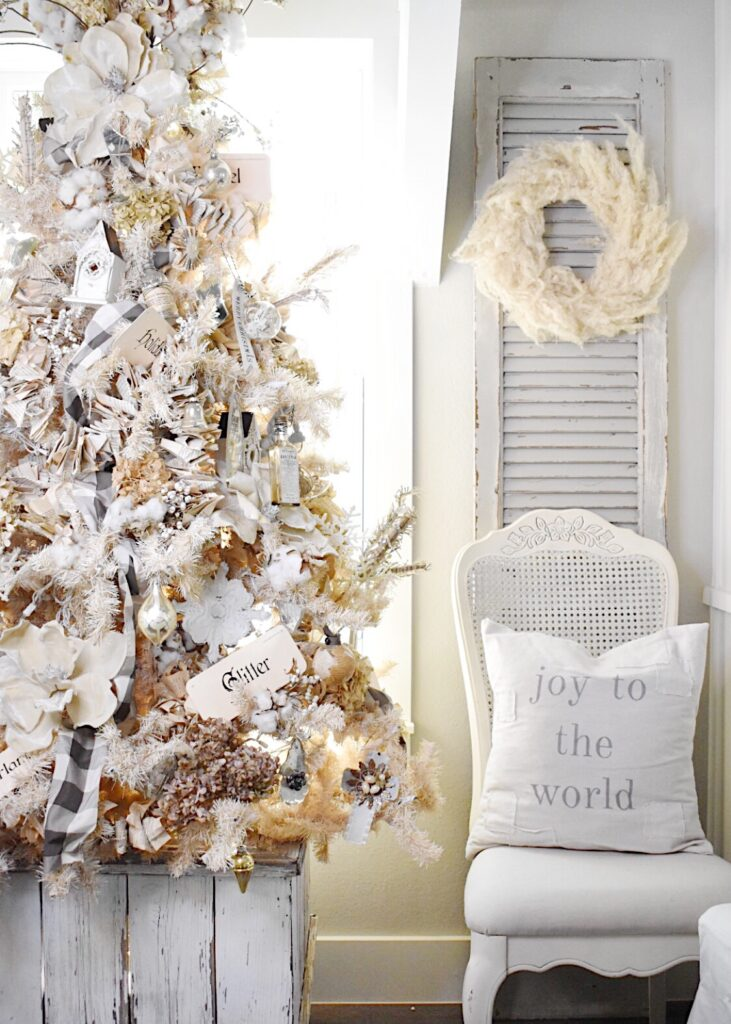 my white vintage living room Christmas tree decorated with all neutral color vintage ornaments and standing in a white vintage planter box.  Beside the tree is a vintage cane back dining chair with a vintage shutter behind it and a wreath made of pampas grass blooms hangs on the wreath