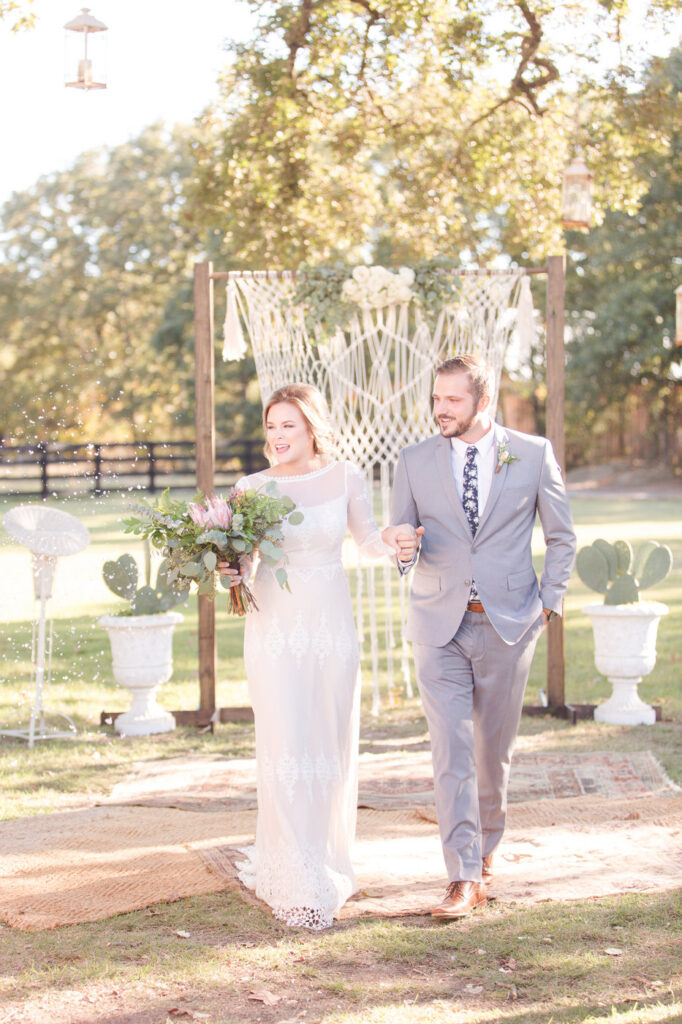 bride and groom walking away from the cermony of an outdoor boho style wedding